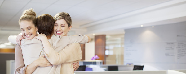 Businesswomen hugging in office