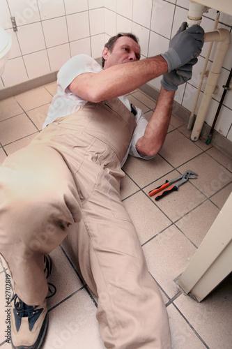 Plumber lying on floor