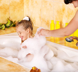 Mother and child washing in bubble bath .