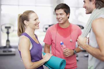 Woman with yoga mat talking to men in gymnasium
