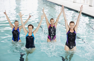 Portrait of smiling women with arms raised in swimming pool