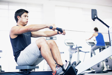 Young man exercising on rowing machine in gymnasium