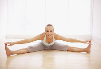 Portrait of smiling woman stretching with legs apart