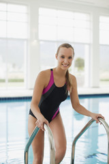 Smiling woman in bathing suit stepping out of swimming pool