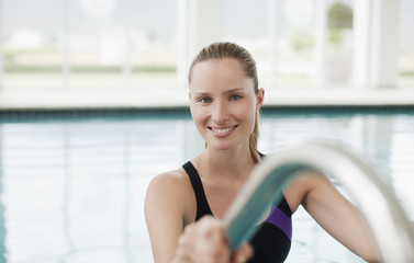 Portrait of smiling woman leaning on ladder in swimming pool