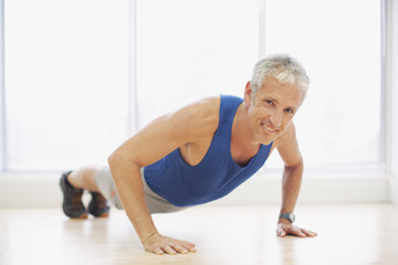 Portrait of smiling man doing push-ups in fitness studio