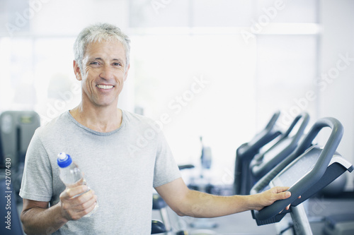 Portrait of smiling man holding water bottle on treadmill in gymnasium