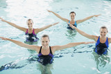 Portrait of smiling synchronized swimming team in swimming pool