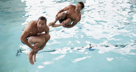 Men doing cannonball dives into swimming pool