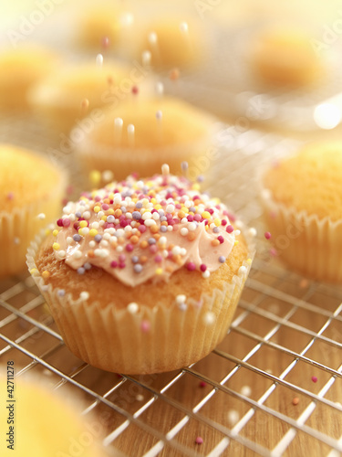 Sprinkles falling on frosted cupcake