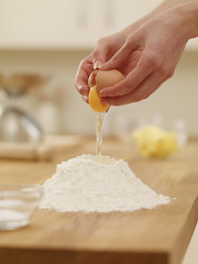 Woman cracking egg over flour nest
