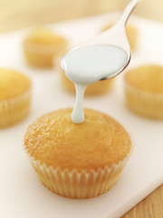 Spoon of icing dripping on cupcake