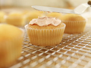Icing being applied to cupcake