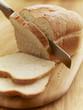 Knife slicing loaf of bread