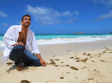young handsome man kneeling by beach