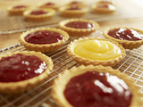 Close up of jam tarts cooling on wire racks