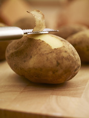 Peeler removing skin from potato