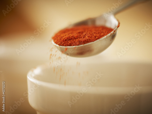 Close up of spice in measuring spoon sprinkling into bowl