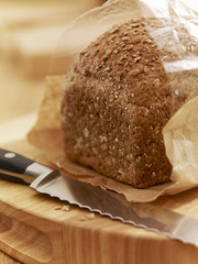 Close up of knife and loaf of bread in wrapper