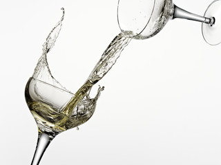White wine pouring from one glass into another