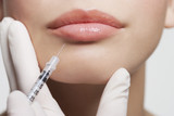 Close up of woman receiving botox injection in lips