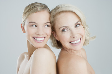 Smiling mother and daughter back to back
