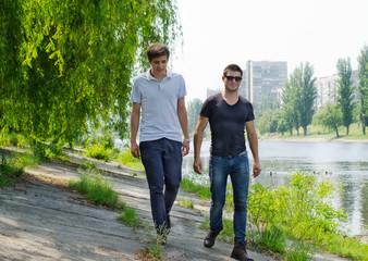 Two young men walking along a riverbank