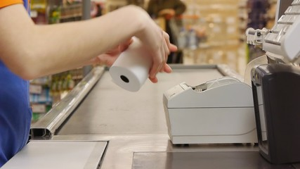 A cashier inserts the tape into the cash register