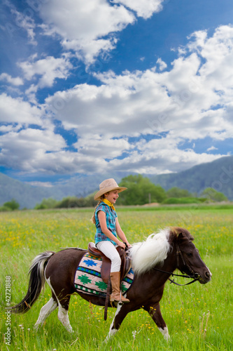 Horse riding - lovely girl is riding a pony