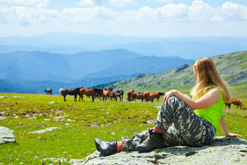 Woman looking to herd of horses
