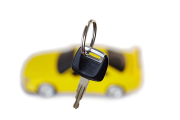 Key from car close up and yellow car in the background