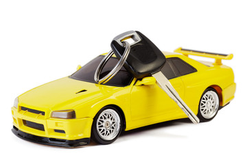Car key lays on the yellow toy car, isolated on white