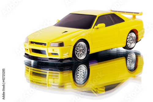Yellow toy car and its reflection isolated on white