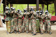 Boys dressed in camouflage stand and aiming with paintball guns