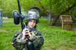 Boy in camouflage suit stands against the paintball area