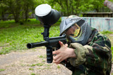 Paintball player in camouflage uniform and protective mask