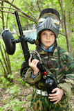 Boy in camouflage stands against brushes on paintball area