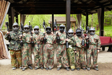 A group of boys in camouflage suits with paintball markers