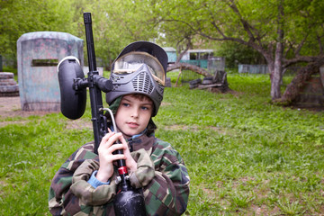 Boy in camouflage with marker for paintball stands