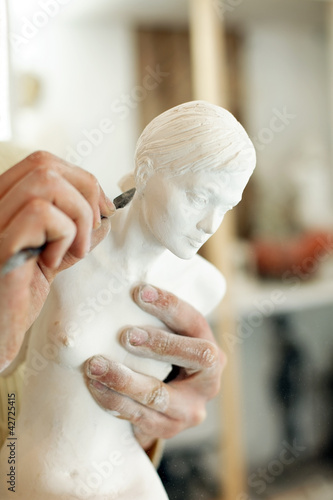 Hands of the sculptor with a statuette and a tool