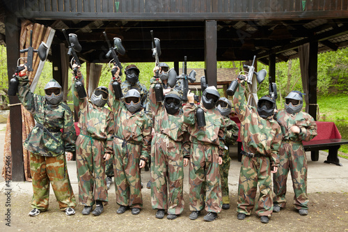 Boys dressed in camouflage stand in a row on a paintball base