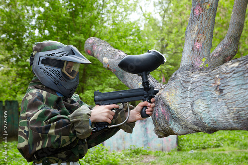 Paintball player in camouflage uniform and protective mask aims