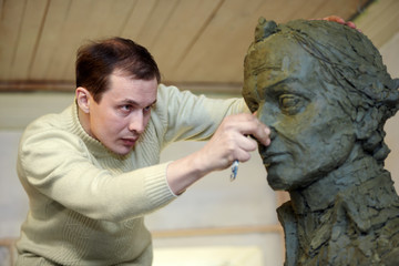 Sculptor works in the studio with plasticine model of bust