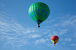 Hot air balloons with people fly in the blue sky.