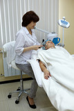 Beautician in beauty salon processes face skin of the patient