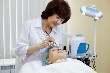 Beautician in beauty salon makes eyebrow tattooing for woman.