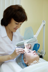 Beautician in beauty salon cleans facial skin of woman