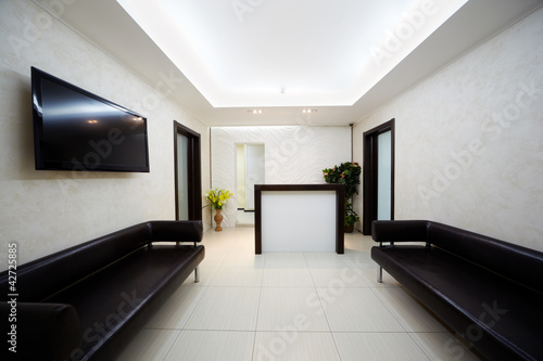 Hallway in beauty salon with two black leather divans