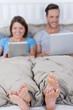 paar mit laptop und tablet im bett