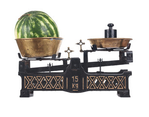 Old-fashioned balance scale with watermelon